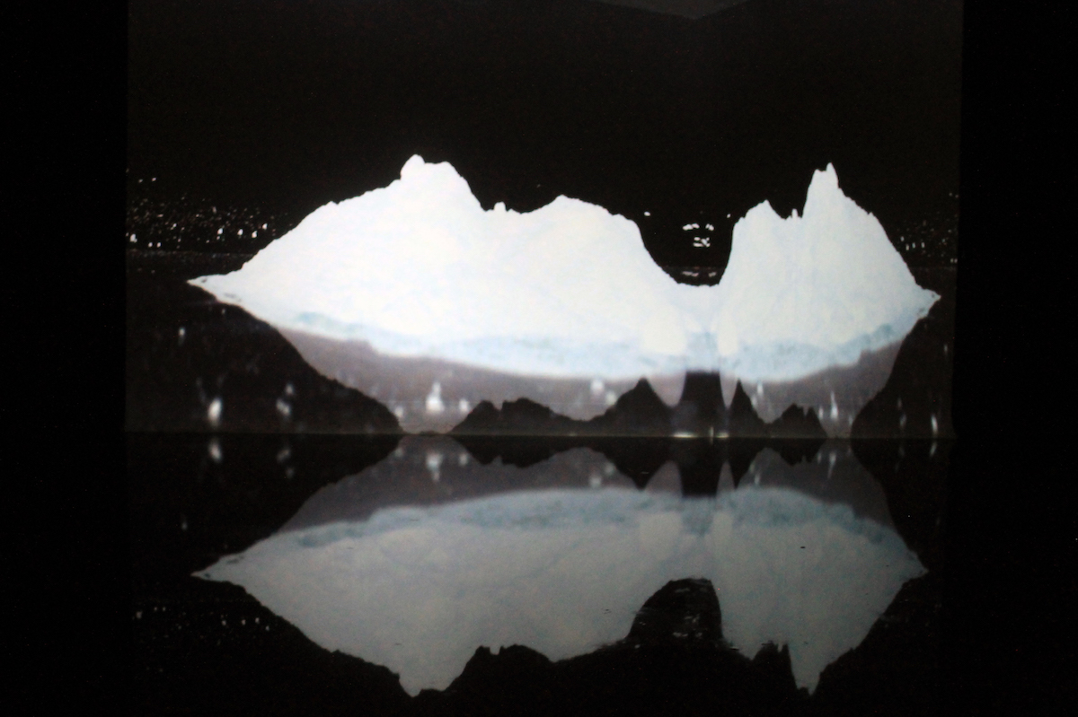 Mateja Šmic, Deconstruction of a mountain / Equilibrium, video installation: 300 x 400 cm basin of Turkish coffee, Video projection, plaster pieces (2019), image courtesy of the artist.